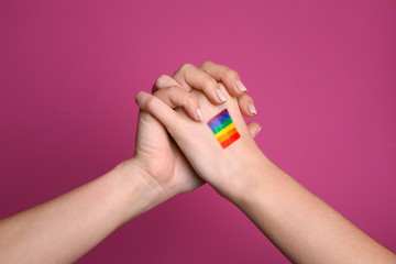 Female hands with painted rainbow flag on color background. Sexual minority concept