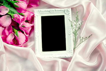 the Empty photo frame with a bouquet sweet pink roses  petal on  soft pink silk fabric , romance and love card concept