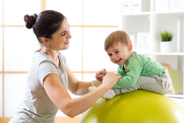 Caring mother doing sport exercises with her kid on fitball