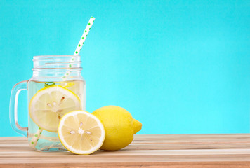 Citrus lemonade water with lemon sliced , healthy and detox water drink in summer on wooden table with blue lighten background