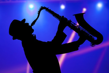 Man playing on saxophone against the background of beautiful light