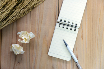 Small note book paper (notepad) for writing information with color pen and crumpled paper balls on wooden table. view from above