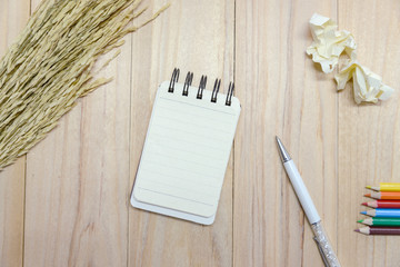 Small note book paper (notepad) for writing information with pen, color pencil and crumpled paper balls on wooden table. view from above