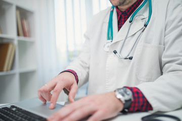 Cropped photo of doctor working on laptop in his office