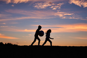 children running on the background of sunset sky
