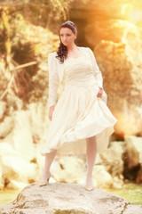 Eine schöne Braut steht auf einem Felsen in einem Gebirgsbach