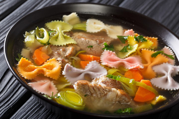 Italian soup with pork, colored farfalle pasta and vegetables close-up. horizontal