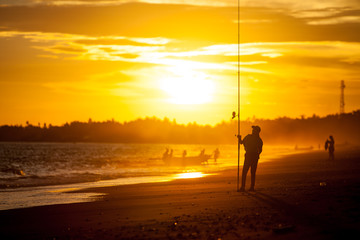 Silhouette of a girl on the beach with a fishing rod in the summer