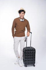 Full length of young tourist asian man holding passport with suitcase over grey background