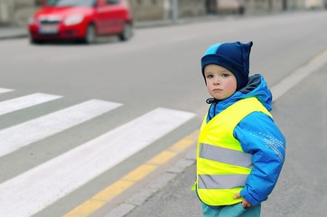 Child in front of pedestrian crossing. Little boy finds out if he can cross the crossswalk. He wears reflective vest because of safety. Car in the background. Child concept. Traffic concept.