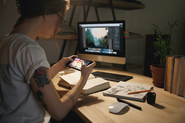 Woman designer sitting indoors at night play games