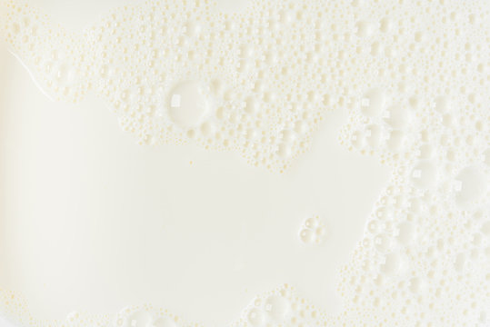 White milk or soy bubble foam background on top view close up