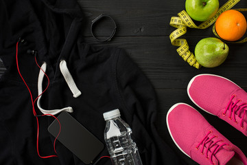 Athlete's set with female clothing, sneakers and bottle of water on dark background