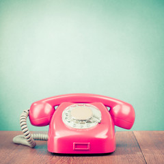 Retro old telephone on table front mint green background. Vintage style filtered photo
