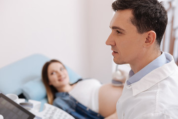 Attentive young sonographer providing appointment in the hospital
