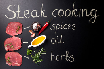 Raw meat. Raw beef steak on blackboard with rosemary and spices. Cooking steak