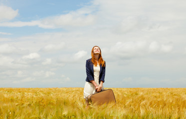 photo of beautiful young woman with suitcase on the wheat field background