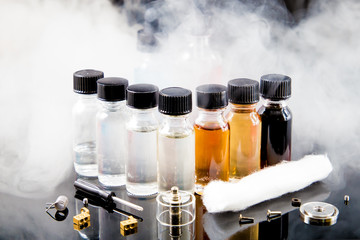 Electronic cigarette liquids with smoke on background