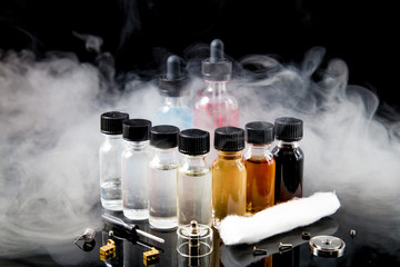 Electronic cigarette liquids with smoke on black background