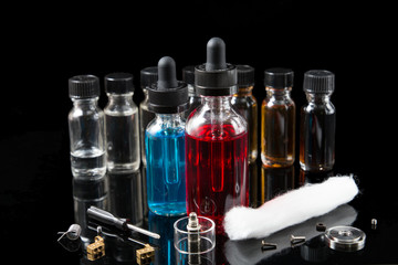 Electronic cigarette liquids and equipment on black background