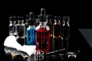Electronic cigarette liquids with equipment on black background