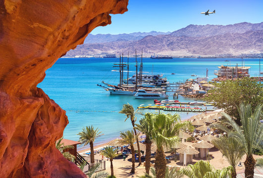 Image with central public beach of Eilat - famous resort city in Israel. Image symbolizes vacation, resting and recreation