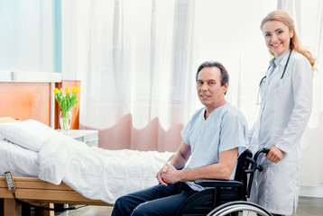 elderly man sitting in wheelchair and doctor standing near him in hospital