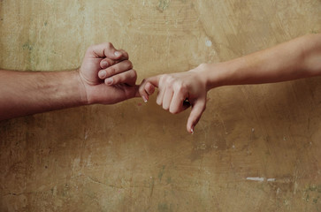 Male and female hands touching each other with little fingers