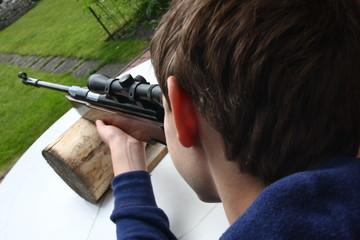 Junge schießt mit einem Luftgewehr