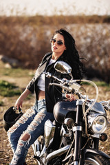 Beautiful brunette woman with a classic motorcycle (cinema bleach bypass effect)