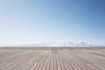 empty wooden floor with white snow mountains