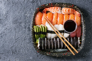 Sushi Set nigiri and sushi rolls in plastic food delivery box with soy sauce and chopsticks over black stone texture background. Top view with space. Japan menu