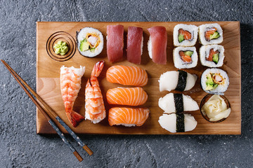 Foto op Aluminium Sushi bar Sushi Set nigiri and sushi rolls on wooden serving board with chopsticks over black stone texture background. Top view with space. Japan menu