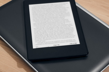 E-Reader With Blurred Text Over Closed Laptop On Wooden Background Closeup