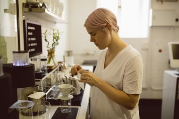 Female barista preparing filter funnel