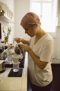 Female barista pouring hot water through funnel