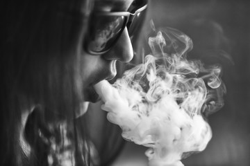 Vape. Young handsome white girl in sunglasses is admiting puffs of steam from the electronic cigarette. Vaping. Teenager. Black and white photo.