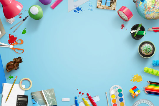 Back to school background image with free space for text ind middle. Stationery, toys, drawing and learning accessories beside.Top view of blue work desk.