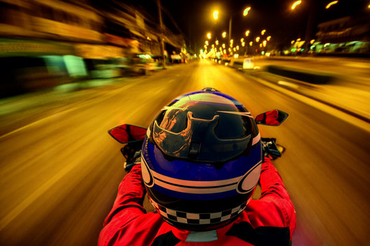 Man riding motorcycle on night road with speed for motion blur