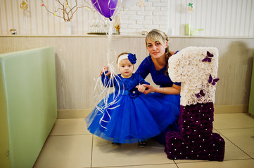 Cute little baby girl at blue dress near 1 year birthday number with mother.