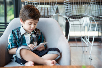 Young asian boy sitting and holding smartphone.