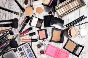 Collection of cosmetics for make-up artist. Powder, blush, highlighter, pigments, glitter, brushes, nude eyeshadow, cushion and eyeliner. studio photo on a wooden background