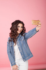 girl in denim jacket make photo on phone pink