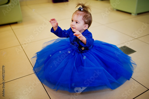364f9bb89 Cute little baby girl at blue dress play with soap bubbles. 1 year ...