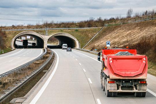 Big industrial tipper truck on asphalt road, rear view, industrial transportation concept