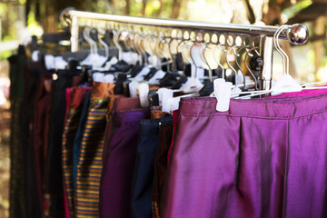 Women clothes made from Thai eastern silk hanging on rack in market