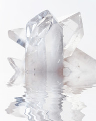 Transparent rock crystals on white reflected in a water