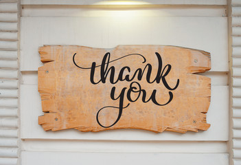 Blank wood board on wall and text Thank you. Calligraphy lettering hand draw
