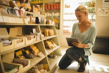 Saleswoman using digital tablet by products on shelves