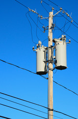 Two electrical transformers on a pole with wires blue sky.